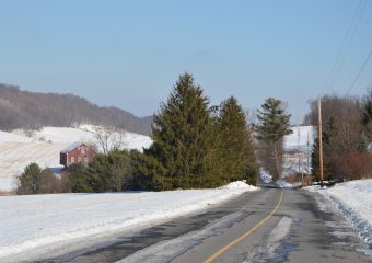 A snowy landscape with a country road passing by a red barn and a stand of evergreen trees