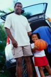 A father standing with his daughter who is holding a basketball