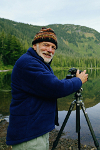 An elderly man taking a photo at a lake